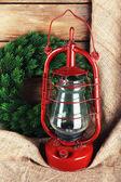 Kerosene lamp with wreath on wooden planks background — Stock Photo