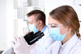 Young female and male scientists  with microscope in laboratory — Foto de Stock