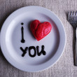 Cookie in form of heart on plate with inscription I Love You, on napkin background — Stock Photo #63964559