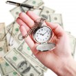 Silver pocket clock in hand on money background. Time is money concept — Stock Photo #63965869