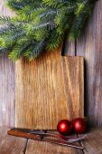 Cutting board with Christmas decoration on wooden planks background — Stock Photo
