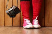 Flicka i sneakers med retro kamera — Stockfoto