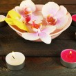 Bowl with orchids and candles on wooden background — Stock Photo #63970285