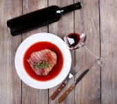 Grilled steak in wine sauce with bottle of wine on wooden background — Stock Photo