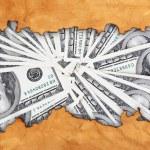 Dollars through torn craft paper — Stock Photo #64267615