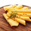 Sliced cheese with dill on wooden cutting board isolated on white background — Stock Photo #64268363