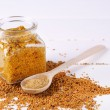 Mustard in glass jar and mustard powder in spoon on wooden background — Stock Photo #64268865