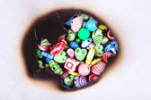 Multicolor beads through hole in white paper — Stock Photo