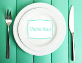 "Plate with text ""Thank you"", fork and knife on color wooden background — Stock Photo"