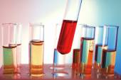 Test tube filled with red liquid on background of other tubes, close-up — Stock Photo