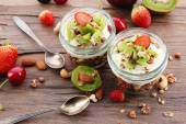 Healthy layered dessert with muesli and fruits on table — Fotografia Stock