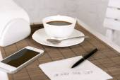 Cup of coffee with mobile phone, pen and phone number on napkin on table with bamboo mat and white wall background — Zdjęcie stockowe