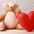 Teddy Bear with red heart on festive background — Stock Photo #64271111