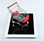 Tablet with small shopping cart isolated on white background — Stock Photo