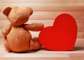 Teddy Bear with red heart on wooden background — Stock Photo