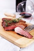 Steak with herbs on wooden stand and wine on table close up — Stockfoto