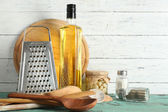 Wooden utensils with metal grater and cutting board on color table and planks background — Stock Photo
