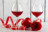 Composition with red wine in glass, red roses and decorative heart on color wooden background — Foto de Stock
