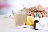 Hot tea for colds, pills and handkerchiefs on table on bright background — Stock fotografie