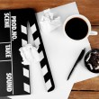 Movie clapper with cup of coffee and ashtray with cigarette butts — Stock Photo #64351845