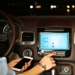 Woman using smart phones while driving at night, close-up — Stock Photo #64353337