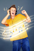 Young man with headphones listening music on grey background — Stock Photo