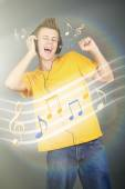 Young man with headphones listening music on bright background — Stock Photo