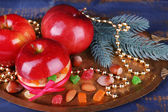 Christmas red apples stuffed with dried fruits on metal tray on color wooden table background — Stok fotoğraf