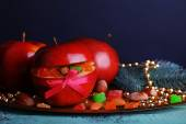 Christmas red apples stuffed with dried fruits on metal tray on color wooden table and dark background — Zdjęcie stockowe