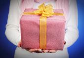 Dárková krabička v ženské ruce na barvu pozadí — Stock fotografie