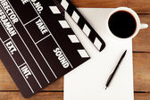 Movie clapper with paper, pen and cup of coffee on wooden planks background — Stock Photo