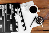 Movie clapper with cup of coffee and ashtray with cigarette butts — Stock Photo