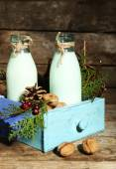 Bottles of fresh milk with natural decor, on wooden background — Stok fotoğraf