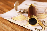 Spyglass, pocket watch and world map on wooden table background — Stock Photo