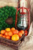 Kerosene lamp with wreath and oranges in wicker basket on wooden planks background — Stock Photo