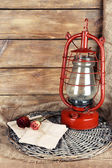 Kerosene lamp with dried rose and letter on wicker mat and wooden planks background — Stock Photo