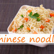 Chinese noodles with vegetables in bowl on bamboo mat background and space for your text — Stock Photo #64406931