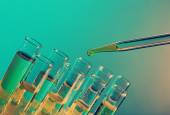 Pipette adding fluid to the one of test-tubes on bright background — Foto Stock