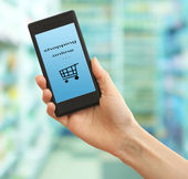 Mobile shopping concept. Hand holding mobile phone for internet shopping on supermarket background — Stock Photo