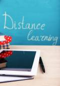 Distance learning concept with tablet and books on blackboard background — Stock Photo
