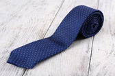 Trendy tie on color wooden background — Stock Photo