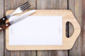 Cutting board with menu sheet of paper on rustic wooden planks background — Photo