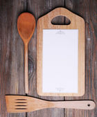 Cutting board with menu sheet of paper on rustic wooden planks background — ストック写真