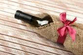 Wine bottle wrapped in burlap cloth on wooden planks background — Fotografia Stock