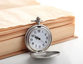 Silver pocket clock and book on white table — Stock Photo