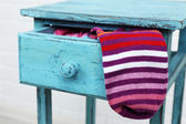 Socks in color drawer on white brick wall background — Stock Photo