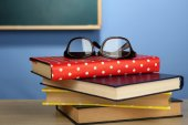 Stack of books with glasses on wooden desk, on colorful wall and blackboard background — Stockfoto