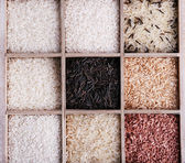 Different types of rice in box on wooden background — Stock Photo