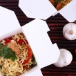 Chinese noodles in takeaway boxes on bamboo mat background — Stock Photo #64746437