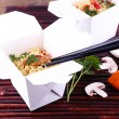 Chinese noodles in takeaway boxes on bamboo mat on wooden background — Stock Photo #64746453